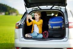 Menina adorável pronta para ir em férias com seus pais Caçoe o jogo com seu telefone em um carro Imagens de Stock