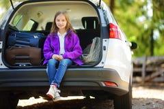 Menina adorável pronta para ir em férias com seus pais Caçoe o relaxamento em um carro antes de uma viagem por estrada Imagens de Stock Royalty Free