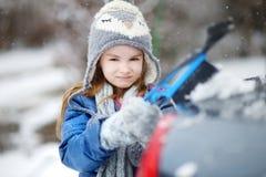 Menina adorável que ajuda a escovar uma neve fotografia de stock