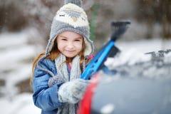 Menina adorável que ajuda a escovar uma neve imagens de stock royalty free