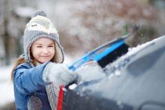 Menina adorável que ajuda a escovar uma neve imagem de stock