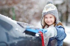 Menina adorável que ajuda a escovar uma neve foto de stock royalty free