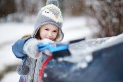 Menina adorável que ajuda a escovar uma neve fotos de stock royalty free