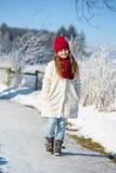 Menina adorável que anda na floresta do inverno em um dia ensolarado Imagens de Stock