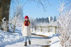 Menina adorável que anda na floresta do inverno em um dia ensolarado Fotografia de Stock