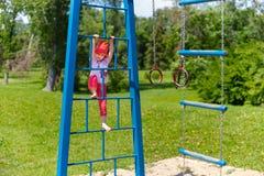 Menina adorável que aprecia seu tempo no parque de escalada da aventura no dia de verão morno e ensolarado Atividades do verão pa fotografia de stock