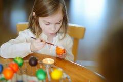 Menina adorável que colore um ovo da páscoa fotos de stock royalty free