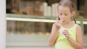 Menina adorável que come o gelado fora no verão Criança bonito que aprecia o gelato italiano real em Roma vídeos de arquivo