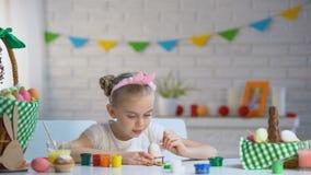 Menina adorável que decora ovos da páscoa com pintura colorida, criança talentoso filme