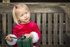 Menina adorável que desempacota seu presente em um banco fotografia de stock