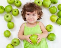 Menina adorável que encontra-se com maçãs verdes imagem de stock