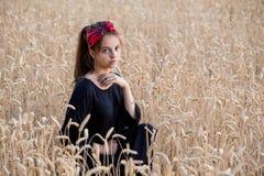 Menina adorável que está no campo de trigo foto de stock