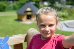 Menina adorável que faz o selfie no campo de jogos fora Fotos de Stock Royalty Free