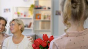 Menina adorável que guarda as tulipas, felicitando pais o 8 de março, presente surpreendente filme