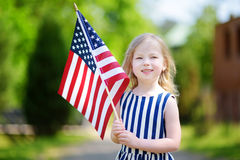 Menina adorável que guarda a bandeira americana fora no dia de verão bonito Imagens de Stock Royalty Free