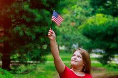 Menina adorável que guarda a bandeira americana fora no dia de verão bonito Fundo do grunge da independência Day Fotos de Stock Royalty Free