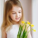 Menina adorável que guarda narcisos amarelos pela janela imagens de stock