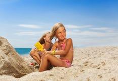 Menina adorável que joga com a areia na praia Fotos de Stock Royalty Free