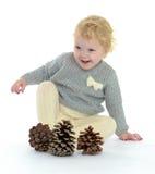 Menina adorável que joga com cones do pinho Imagem de Stock