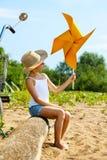 Menina adorável que joga com moinho de vento de papel Imagens de Stock Royalty Free