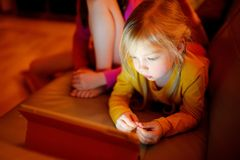 Menina adorável que joga com uma tabuleta digital em uma sala escura Crianças que têm o divertimento junto em casa fotografia de stock