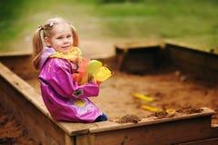 Menina adorável que joga em uma caixa de areia Fotos de Stock Royalty Free