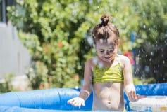 Menina adorável que joga em uma piscina Fotografia de Stock Royalty Free