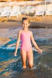 Menina adorável que joga no mar em uma praia Foto de Stock Royalty Free