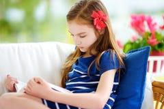 Menina adorável que lê um livro na sala de visitas branca no dia de verão bonito Imagem de Stock