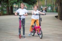 Menina adorável que monta uma bicicleta no dia de verão bonito fora Imagens de Stock Royalty Free