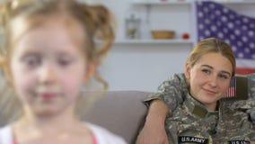 Menina adorável que olha in camera, pais militares orgulhosos que sentam o sofá, patriotismo vídeos de arquivo