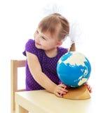 Menina adorável que olha um globo e sonhos Fotos de Stock