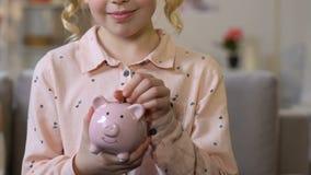 Menina adorável que põe a moeda no mealheiro, fundos da primeira infância, close up video estoque