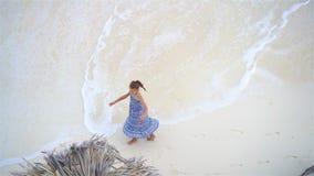 Menina adorável que tem muito divertimento na água pouco profunda Vista de cima de uma praia abandonada com água de turquesa video estoque