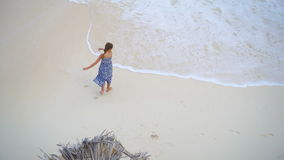 Menina adorável que tem muito divertimento na água pouco profunda Vista de cima de uma praia abandonada com água de turquesa vídeos de arquivo