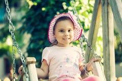 Menina adorável que tem o divertimento em um balanço exterior foto de stock