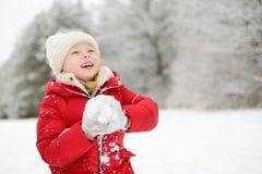Menina adorável que tem o divertimento no parque bonito do inverno Criança bonito que joga em uma neve foto de stock