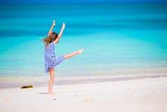 Menina adorável que tem o divertimento que faz o cartwheel no Sandy Beach branco tropical Foto de Stock