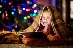 Menina adorável que usa um PC da tabuleta por uma chaminé na noite do Natal Fotografia de Stock