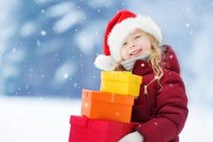 Menina adorável que veste o chapéu de Santa que guarda uma pilha de presentes do Natal no dia de inverno bonito Fotos de Stock