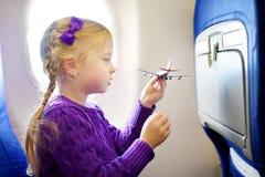 Menina adorável que viaja por um avião Criança que senta-se pela janela dos aviões e que joga com plano do brinquedo Viagem com c fotografia de stock