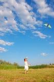 Menina adorável que voa um papagaio Fotografia de Stock