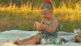 A menina adorável senta-se na cobertura no parque e verifica-se o dinheiro para ver se há a autenticidade vídeos de arquivo