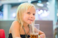 A menina adorável tem a refeição com bebida da soda e batatas fritadas no fá Imagens de Stock