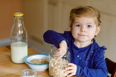 Menina ador?vel da crian?a que come farinhas de aveia saud?veis com leite para a crian?a feliz bonito do beb? do caf? da manh? no imagens de stock royalty free