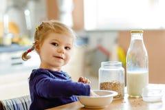 Menina ador?vel da crian?a que come farinhas de aveia saud?veis com leite para a crian?a feliz bonito do beb? do caf? da manh? no foto de stock