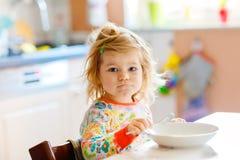 Menina ador?vel da crian?a que come o porrige saud?vel da colher para a crian?a feliz bonito do beb? do caf? da manh? no assento  fotos de stock