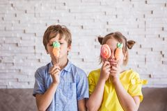 Menina ador?vel e menino que guardam merengues doces coloridas em uma vara no dia da P?scoa foto de stock