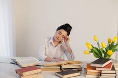 Menina adormecida em uma tabela com livros Fotografia de Stock Royalty Free