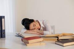 Menina adormecida em uma tabela com livros Fotos de Stock